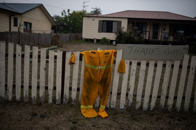 A firefighter's suit hangs on a fence next to a