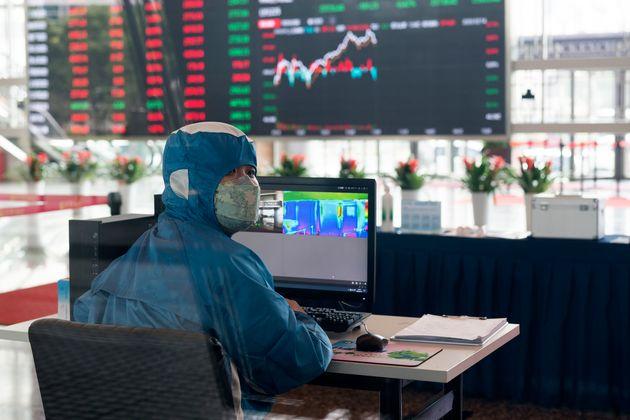 Un trabajador del mercado de cambio de Shanghai, con un traje de protección y controlando la temperatura...