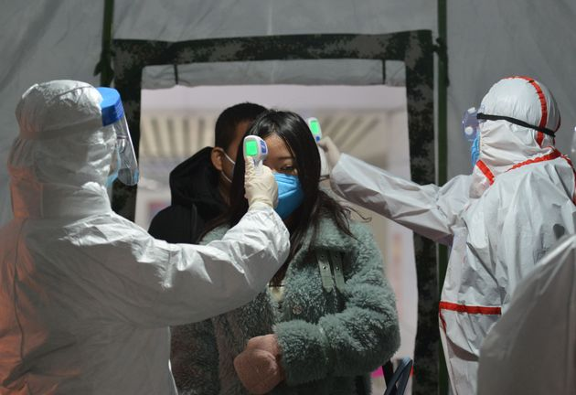 A Chinese government worker checks the travelers' body temperature at the exit of a railway station in...