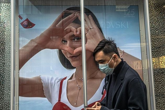 Un hombre pasea junto a uno de los pocos carteles de San Valentín que hay en
