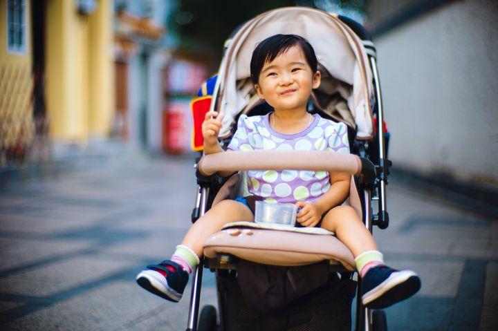 Toddler girl sitting in a stroller smiling joyfully during sunset.