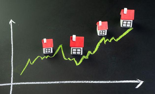 家、不動産、または不動産市場の価格が上がるか、コンセプトが上がる、緑のある小さなミニチュアの家...