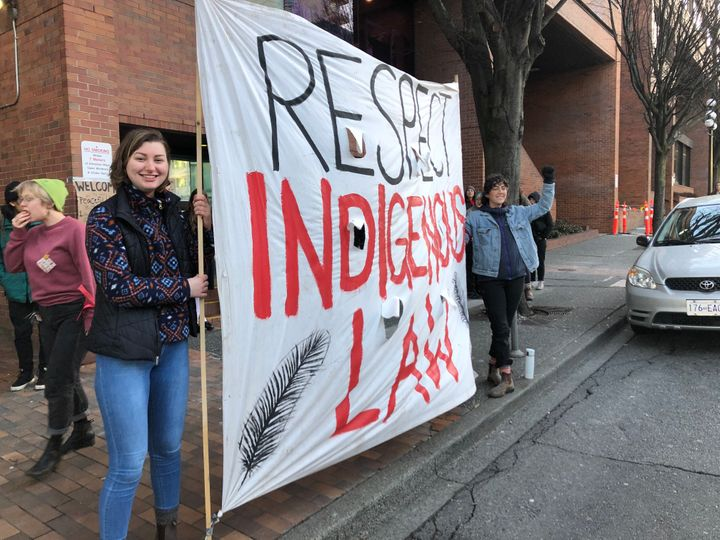 "Allies of the Wet'suwet'en hereditary chiefs stand with a sign reading ""Respect Indigenous Law"" outside a B.C. provincial ministry building in Victoria on Feb. 14, 2020."