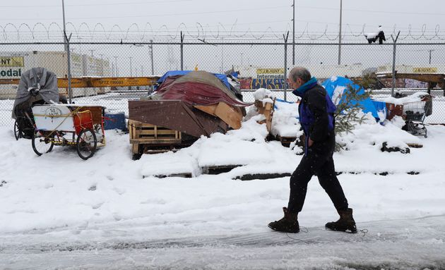 Kevin Shepherd walks back to the tent where he lives as snow falls in Seattle on Feb. 11, 2019. Shepherd,...