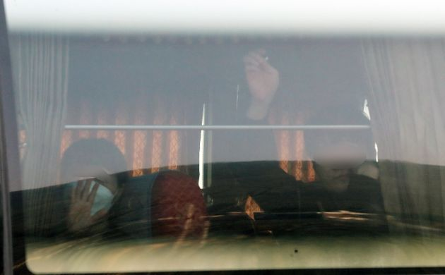 15일 오전 충남 아산시 경찰인재개발원에서 코로나19 사태로 인해 2주간 격리생활을 마치고 퇴소하는 1차 입국 우한 교민들이 버스에 올라 손을 흔들고