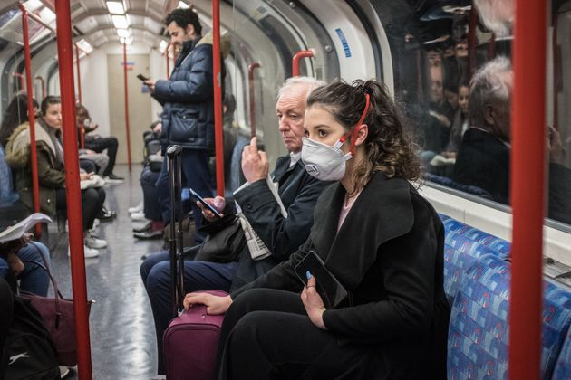 A woman seen on a tube wearing a face mask. A total of nine people in the UK are now being treated for...