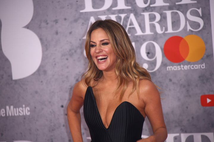 Television presenter Caroline Flack poses for photographers upon arrival at the Brit Awards in London, Wednesday, Feb. 20, 20