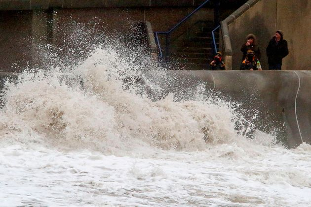 Bystanders take photographs as huge waves crash against the sea wall at Porthcawl, south