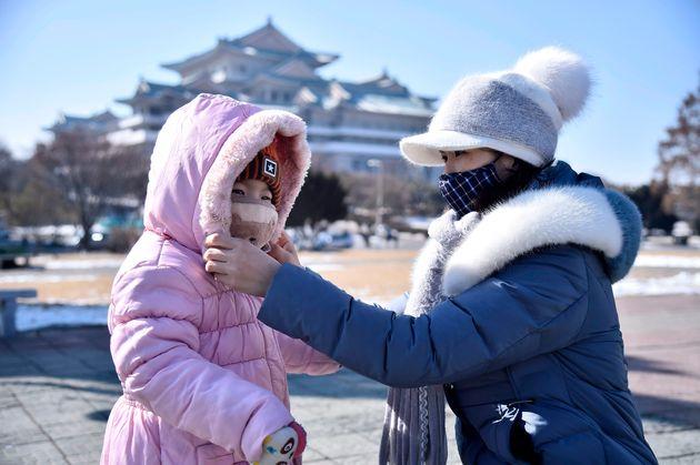 평양 시내에서 한 여성이 딸의 마스크 착용을 도와주고 있다. 평양, 북한. 2020년