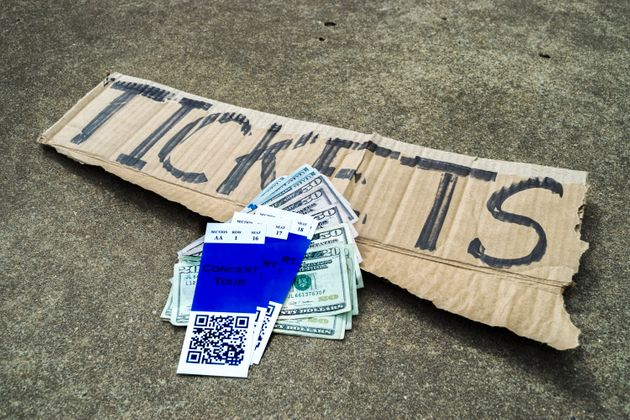 A concert ticket scalper's ticket stubs with QR code, money and his cardboard sign with