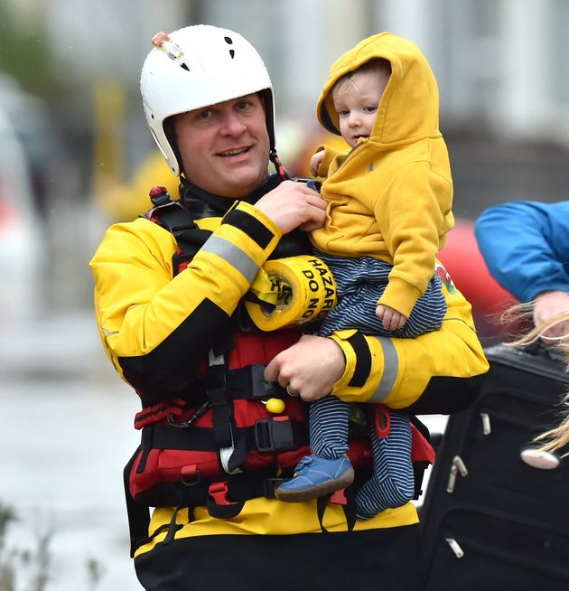 One-year-old Blake is carried by a rescue worker as emergency services continue to take families to safety,...