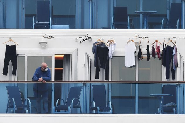 A passengers is seen on a balcony of the Diamond Princess cruise ship, with around 3,600 people quarantined...