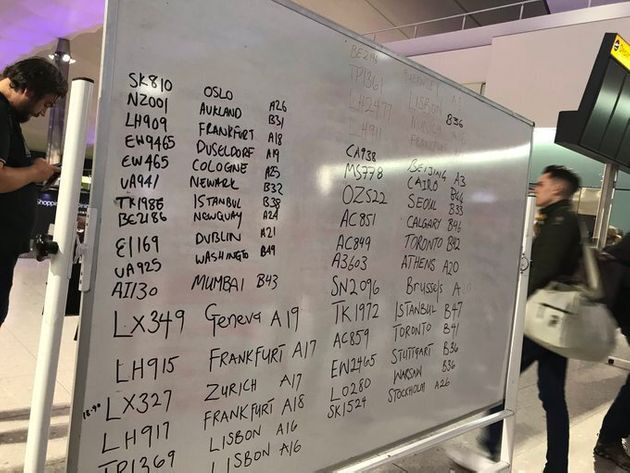 Whiteboards displaying handwritten flight numbers and destinations at Heathrow after the airport experienced...
