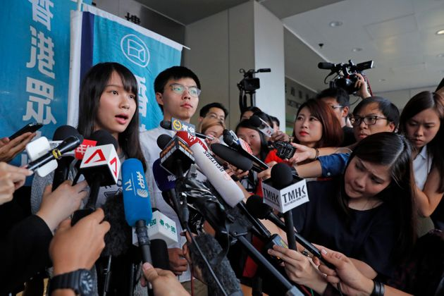 Pro-democracy activists Joshua Wong, right, and Agnes Chow speak to media outside a district court in Hong Kong, Friday, Aug. 30, 2019. Hong Kong activist Joshua Wong and another core member of a pro-democracy group were granted bail Friday after being charged with inciting people to join a protest in June, while authorities denied permission for a major march in what appears to be a harder line on this summer's protests. (AP Photo/Kin Cheung)