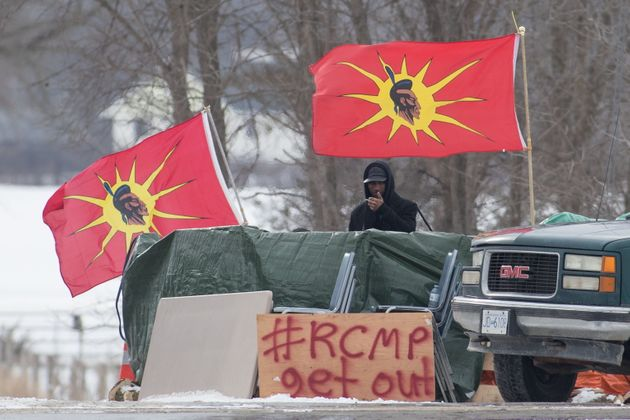 A protester stands between Mohawk Warrior Society flags at a rail blockade near Belleville, Ont., on...