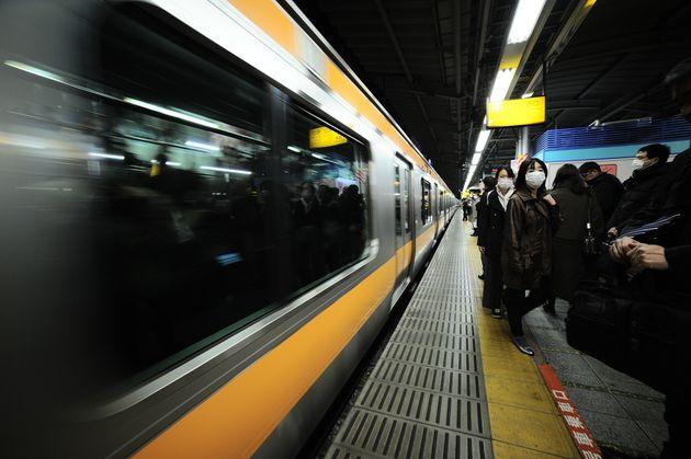 マスクを着けて駅のホームを歩く人たち=2月11日、東京都内