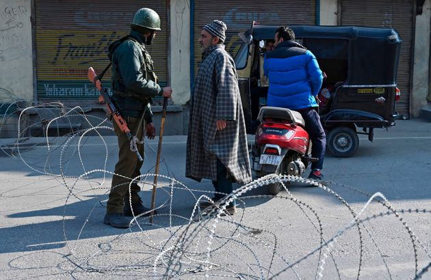 Paramilitary trooper talks to a man at a checkpoint during a one-day strike called by Jammu and Kashmir...
