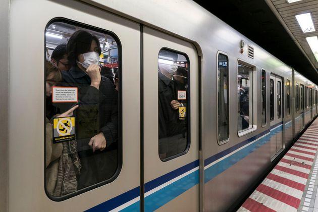 マスクをして満員電車に乗る人々のイメージ