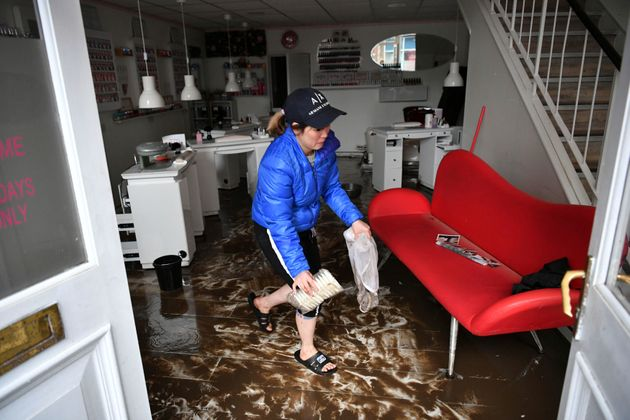 An employee cleans a nail salon, after Storm Dennis hits the UK leading to widespread flooding, in Pontypridd,