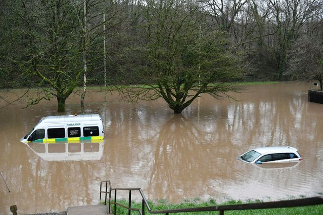 An ambulance, left, and a vehicle are submerged after flooding in Nantgarw,