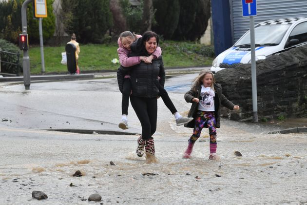 Local residents remain cheerful as walk through receding floodwater in Mountain Ash, Wales as Storm Dennis...