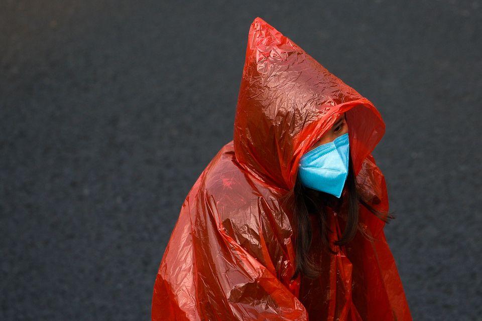 A masked woman in a plastic rain coat walks on a street in Beijing, Tuesday, Feb.