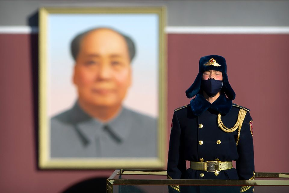 A member of a Chinese honour guard wears a face mask as he stands guard on Tiananmen Square in Beijing,...