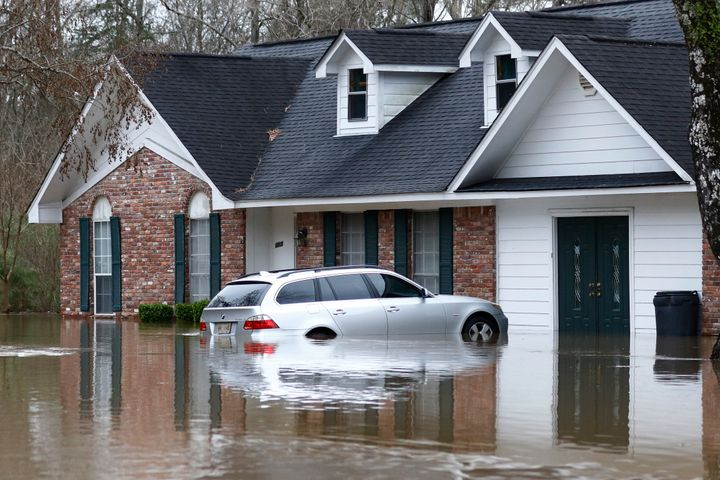 Water from the Pearl River floods this Jackson, Mississippi home and car on Sunday.