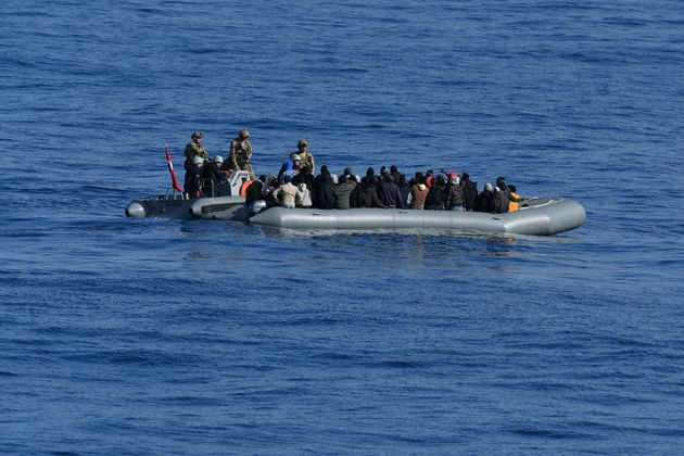 In this image provided by the Turkish Military, members of Turkish forces, left, approach migrants aboard...