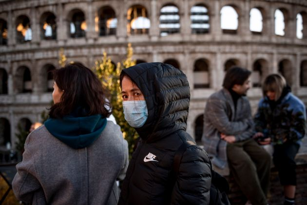 ROME, ITALY - FEBRUARY 6: Chinese tourists wearing face masks visit the Colosseum area on February 6,...
