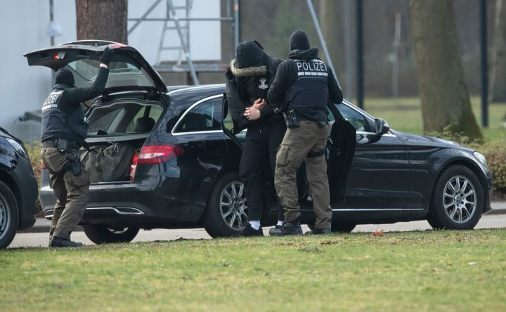 An unidentified person is brought to the Federal Supreme Court by police officers in Karlsruhe, Germany, Saturday, Feb 15, 20