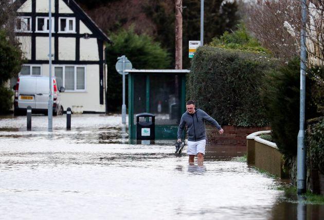 A man wades through flood water in