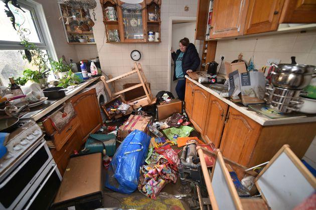 Rachel Cox inspecting flood damage in her kitchen in Nantgarw, south