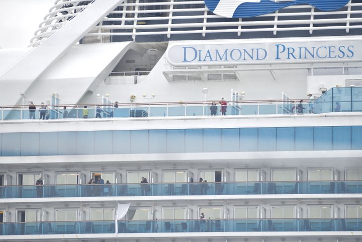 YOKOHAMA, JAPAN - FEBRUARY 15 : Passengers, wearing mask against the coronavirus, are seen on the deck and balconies of Diamond Princess cruise ship docked and in quarantine at the Daikoku Pier Cruise Terminal in Yokohma, Japan on February 15, 2020. Japan still continues to report several case of people infected by the coronavirus Covid-19 since the start of outbreak as well as on board the Diamond Princess cruise ship quarantined in Yokohama Bay for around 15 days. On February 15, during a press conference, Japan's Health Minister said that 67 more people on board of the cruise ship have been infected. (Photo by David Mareuil/Anadolu Agency via Getty Images)