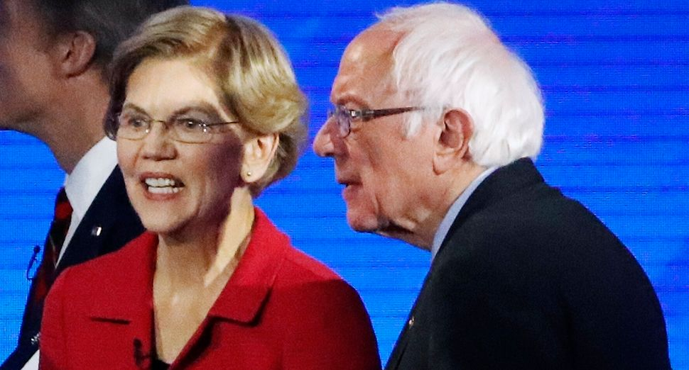 Sen. Elizabeth Warren (D-Mass.) and Sen. Bernie Sanders (I-Vt.) leave the stage after a Democratic presidential primary debat