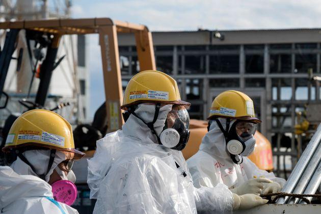 Les combinaisons ne sont pas là pour protéger les ouvriers des radiations, mais des poussières...