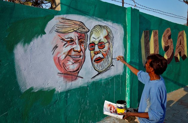 Paintings of US President Donald Trump and Prime Minister Narendra Modi on a wall as part of a beautification,...