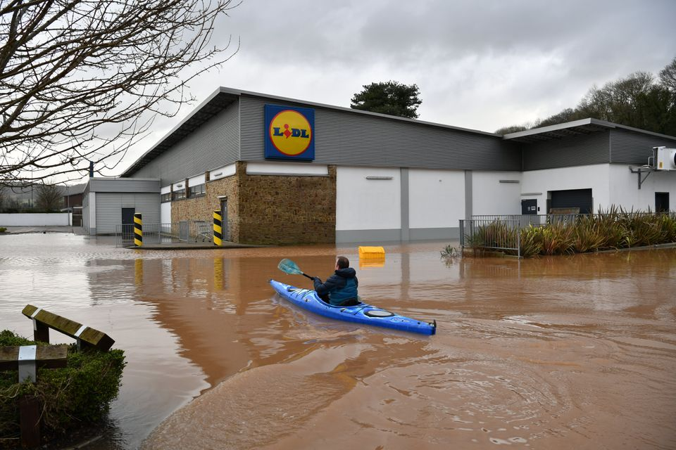 A canoeist makes their way towards Lidl in Monmouth in the aftermath of Storm