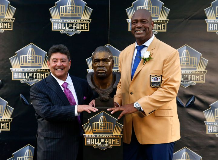 Former NFL player Charles Haley, right, poses with his bust, next to his present, former San Francisco 49ers owner Edward DeB