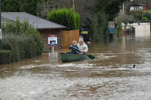 Nearby residents making their way through floodwater by boat in