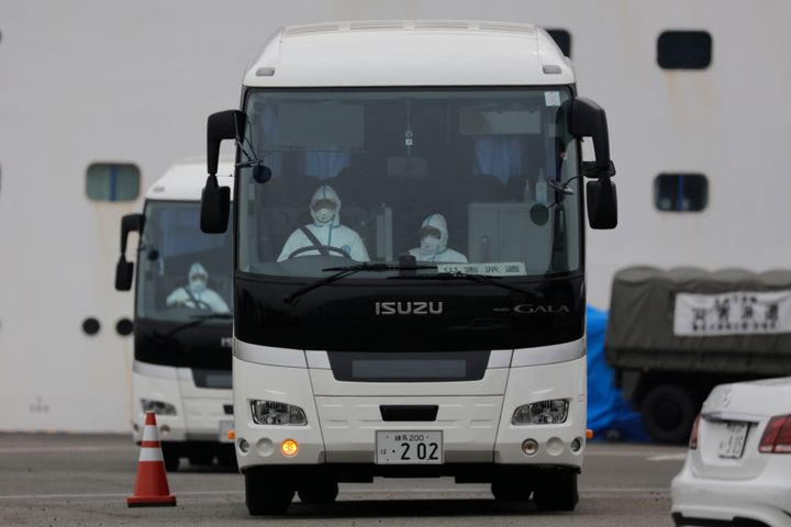 Two buses leave a port where the quarantined Diamond Princess cruise ship is docked in Yokohama on Saturday, Feb. 15.