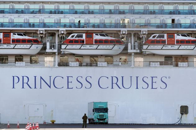 A passenger stands on the balcony of the quarantined cruise ship Diamond Princess on Sunday, Feb.