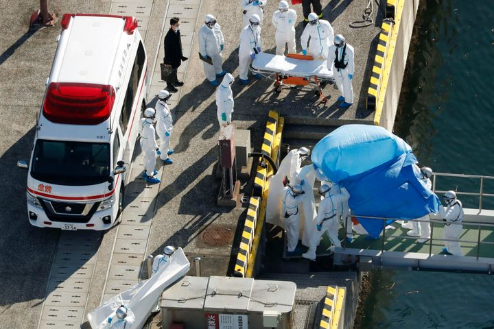 Medical workers in protective suits lead a passenger who tested positive for a new coronavirus on the Diamond Princess cruise ship on Wednesday, Feb. 5.