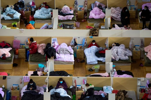 Patients infected with the coronavirus take rest at a temporary hospital converted from the Wuhan Sports...