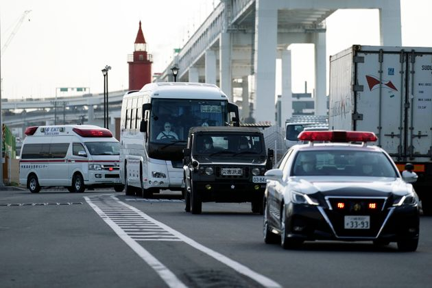 A bus carrying the passengers from the quarantined Diamond Princess cruise ship leaves a port in