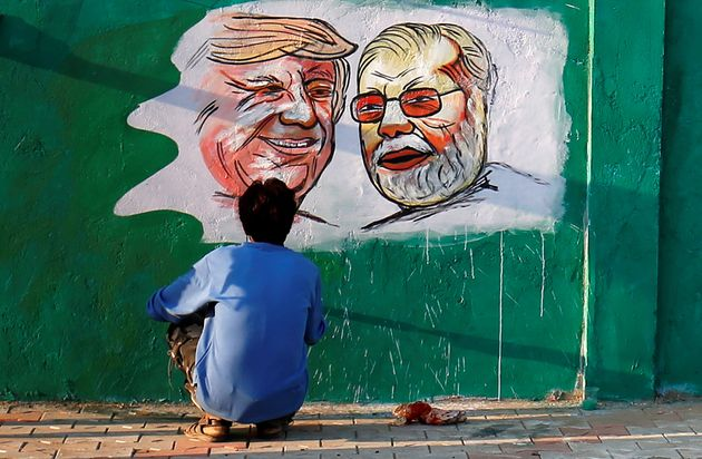 A man applies finishing touches to paintings of U.S. President Donald Trump and Indian Prime Minister...