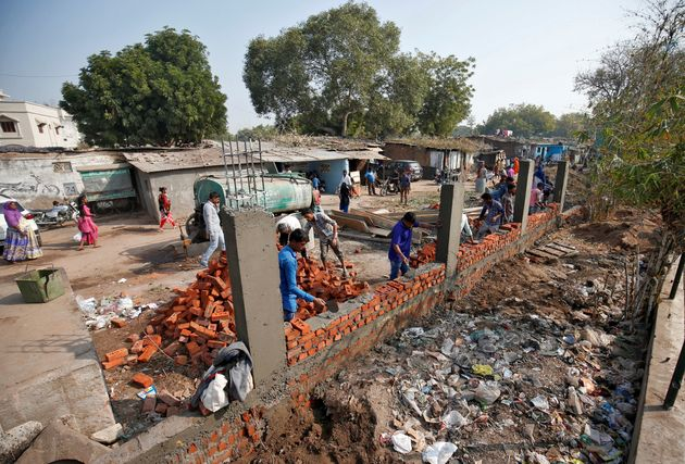 Construction workers in Ahmedabad build a wall along a slum area as part of a beautification drive ahead...