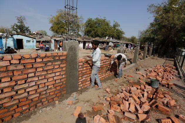 Indianos trabalham na construção do muro que vai esconder uma favela, na cidade de Ahmadabad,