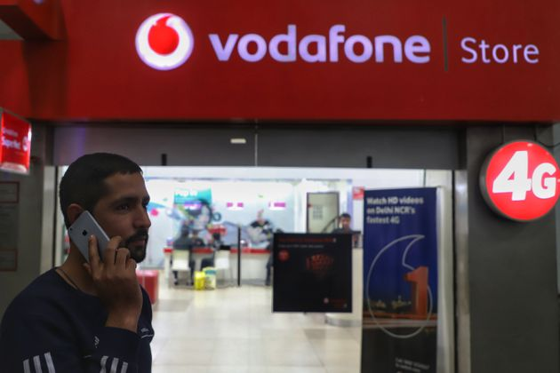 A man talks on a cell phone near a Vodafone showroom in New Delhi on 4 January