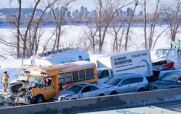 Un pompier passe devant un amoncellement de nombreux véhicules sur la rive sud de Montréal à La Prairie,...